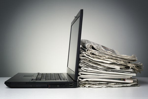 laptop and newspapers on desk