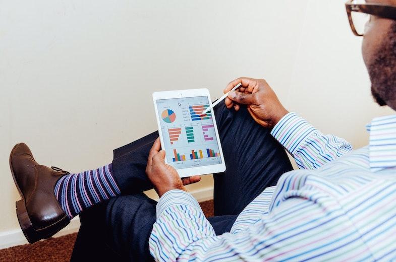 Man sitting with ipad displaying analysis information