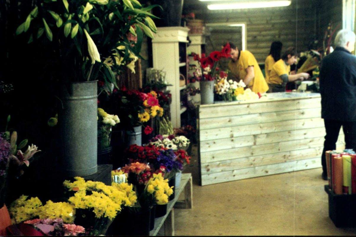 Plusieurs fleurs en pots et des vendeurs en fond