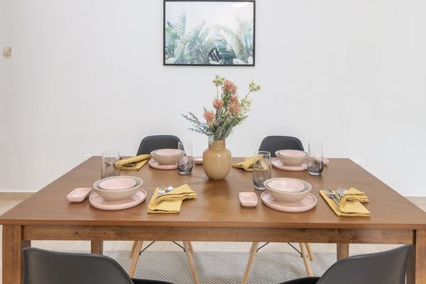 Pinetree condo dining table decorated with pink bowl and plates,  and mustard cloth