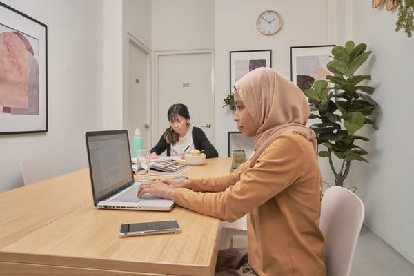 an asian girl and a hijabi woman working and doing work at the dining table at a shophouse