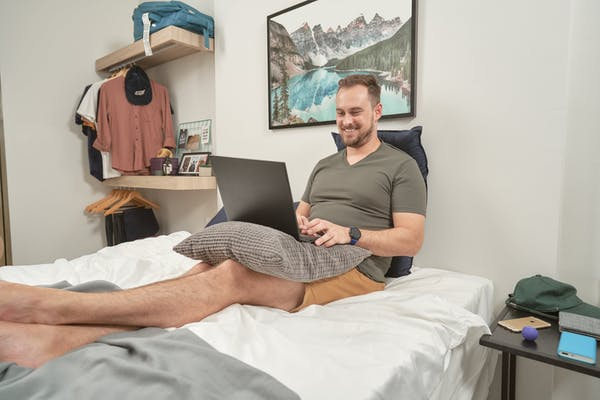 man clicking on laptop on top of bed