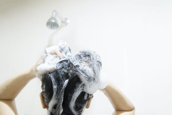 woman showering and lathering head and hair with shampoo