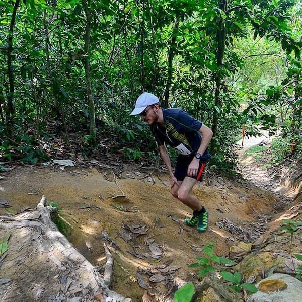 man wearing blue camp hiking up a jungle