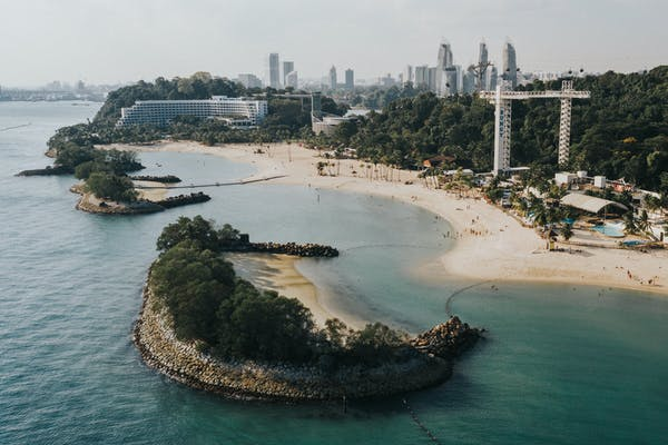 bird's eye view of sentosa beach with few islands, bungee jumping, hotel and jungle