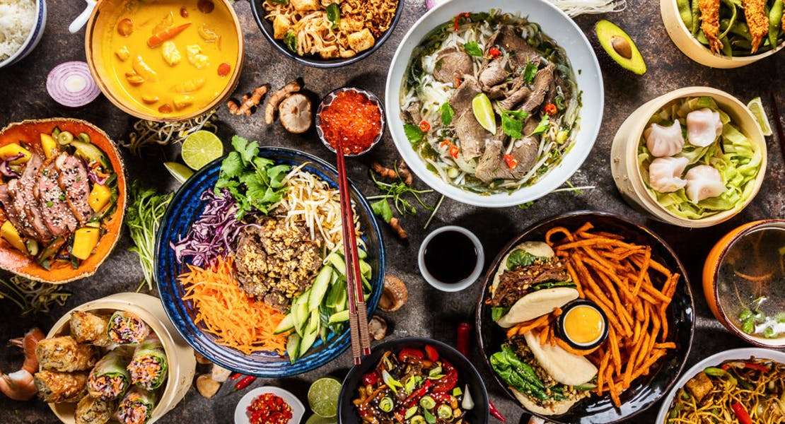 traditional food from around the world being displayed on a table. There are curry, salad, paper spring roll, beef pho, pita, dim sum, ebi and edamame, fried noodles, sweet potato fries, avocado, prawns, fried rice, steamed rice and many raw ingredients and spices