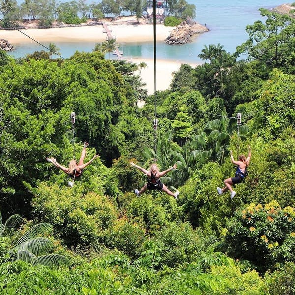 3 women going down a zipline across the forest and beach at sentosa