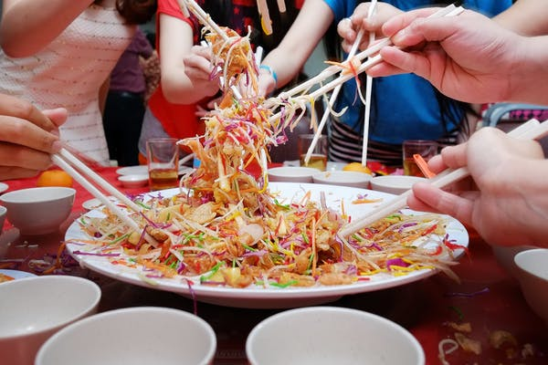 people tossing yu sheng during reunion dinner