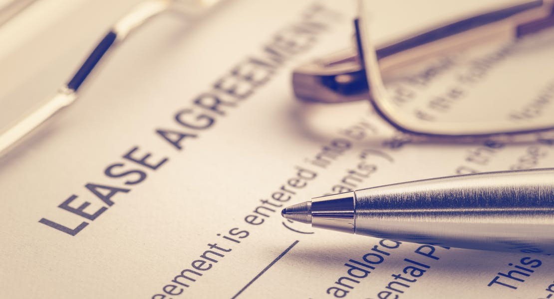 a sample lease agreement contract, a pen is laid over the contract