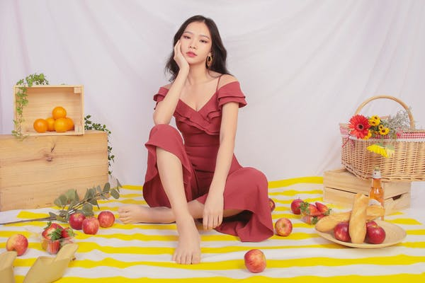 model in soft red dress, with basket of fruits and french loaf all over the picnic mat