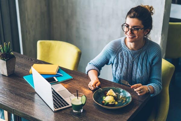 bespectacled woman wearing blue long sleeve shirt eating cake while watching something on her laptop at the dinner table