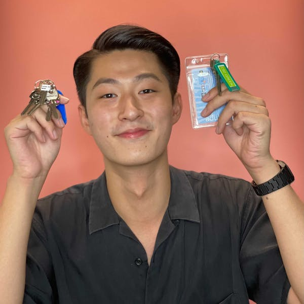 young man holding key and key cards of different properties