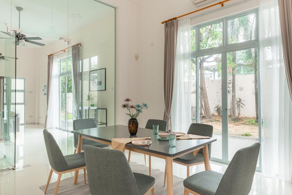 a fully furnished dining area at a landed property in Serangoon. Plates and cups on the table, with a vase centre piece