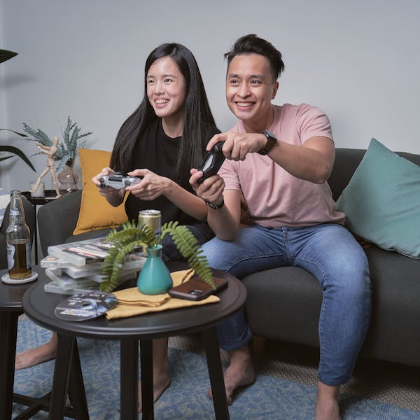 man and woman sitting on the sofa, playing video games
