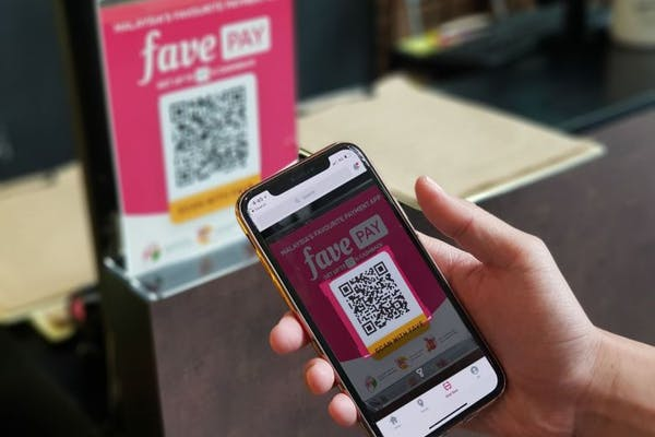 person using iphone to scan favepay QR code