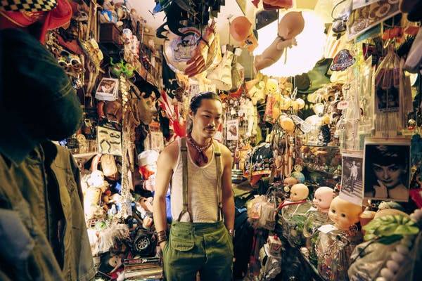man in the middle of a shop selling antique collectibles