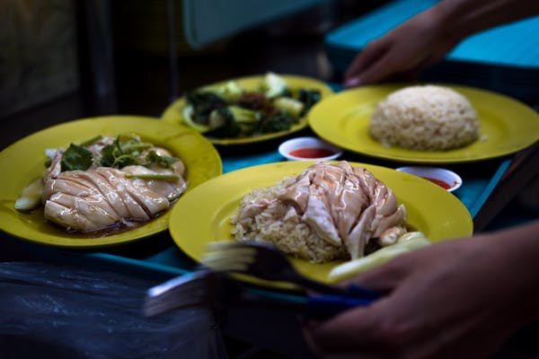 Chicken rice and vegetables served, together with chllli on a tray at a hawker centre in Singapore
