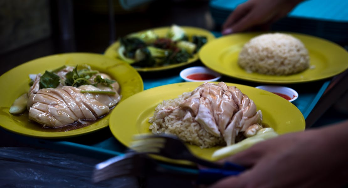 Chiken rice and vegetables served, together with chllli on a tray at a hawker centre in Singapore. Photo by Nauris Pukis.