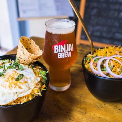 delicious bowls of biryani served with fried egg and papadom, paired with binjai brew