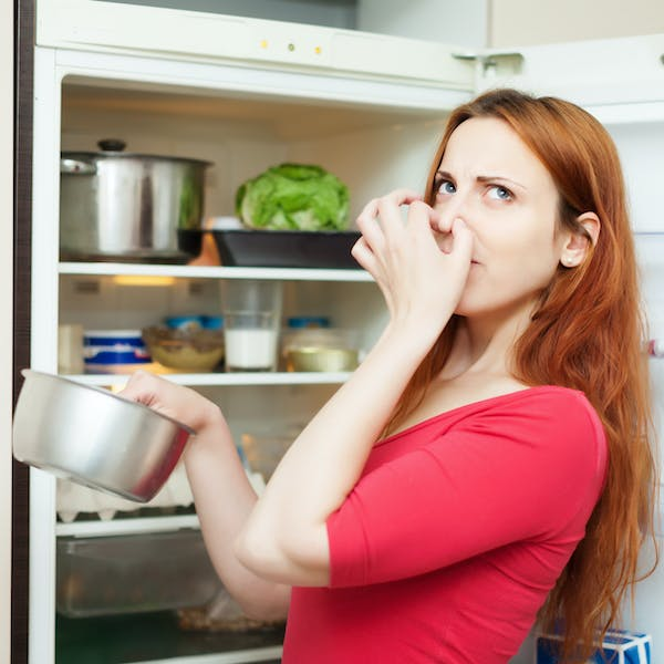 woman in red holding foul food  by the fridge door