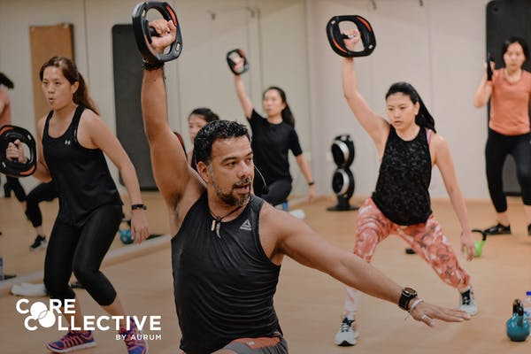 middle aged male instructor teaching fitness class to a group of ladies in a studio