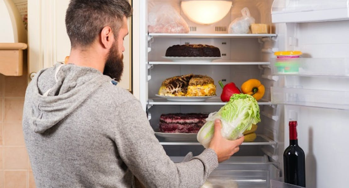 man with lettuce by the refrigerator door