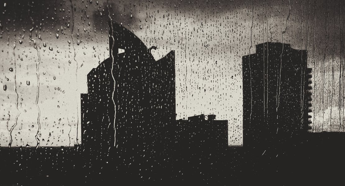 raining on window with buildings