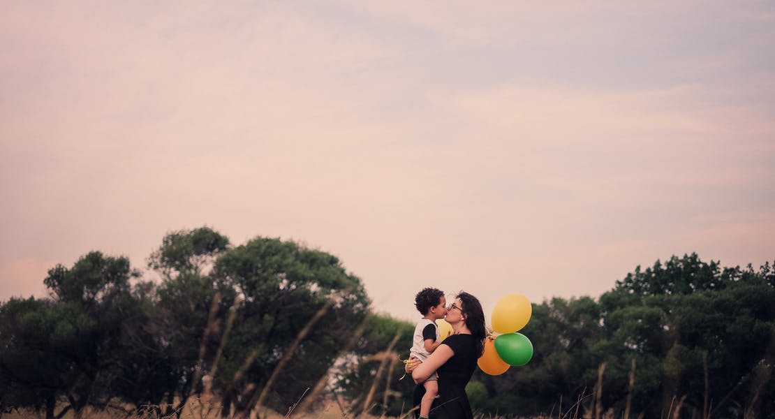 mom kissing baby in a field, holding balloons