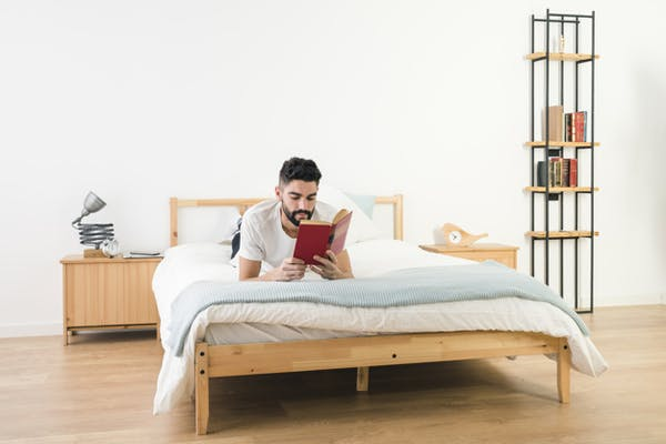 man lying on bed reading book