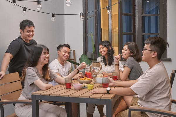 friends hangint out drinking and eating chips at the outdoor deck, laughing and smiling
