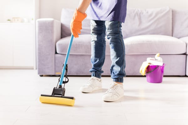 photo of a person mopping his living room, a bucket of detergent can be seen in the background