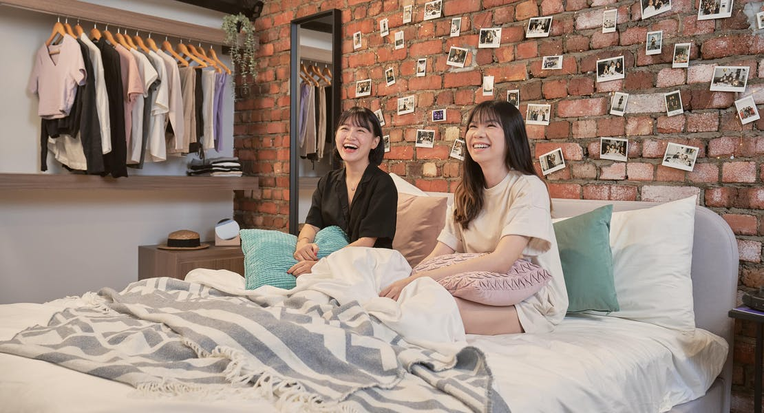 two female friends watching movie comfortable  on the bed