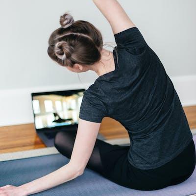 caucasian lady doing yoga, following her laptop