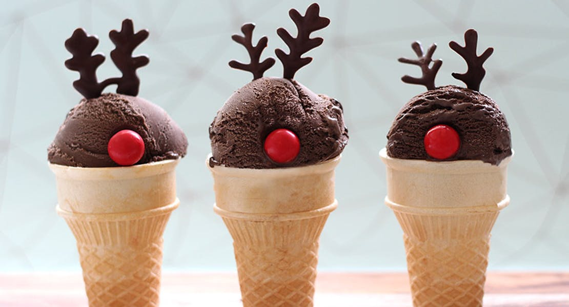 chocolate ice cream on a wafer cone looking like rudolp the red nose reindeer