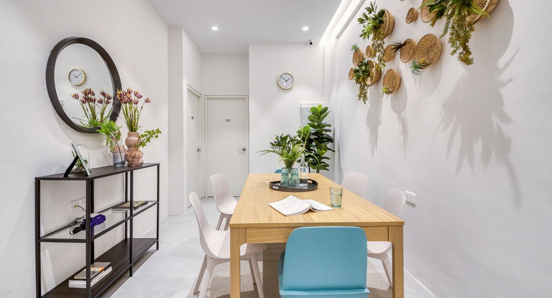 dining area at 460A Geylang Road, with plants in rattan baskets decked on to the wall