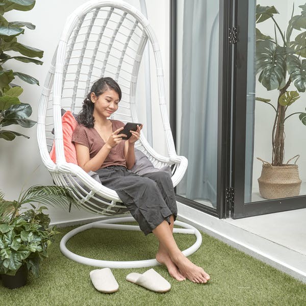 a woman sitting on a swing chair at the outer deck, reading a storybook from her Kindle