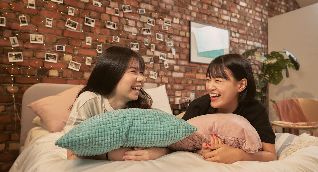 two young ladies hanging out on bed, laughing