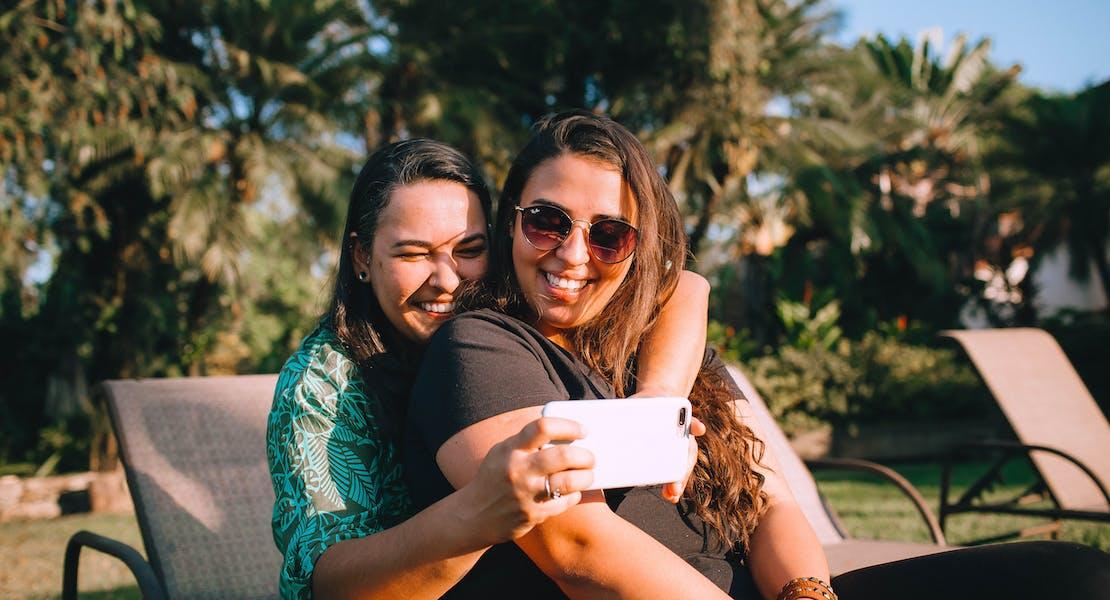 two girl besties taking a selfie by the pool