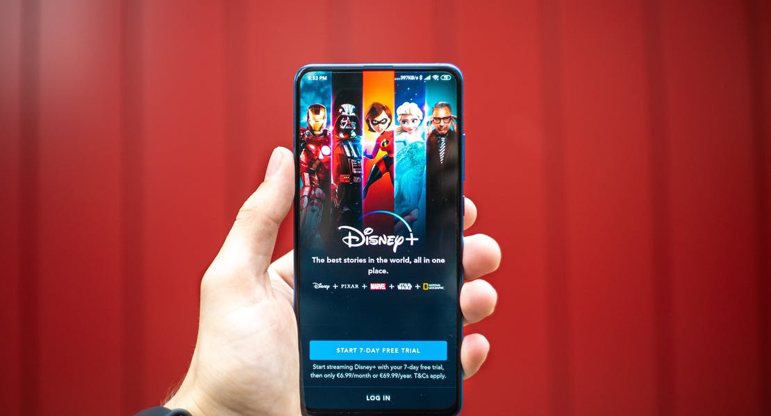 hand holding a phone showing screen of Disney+