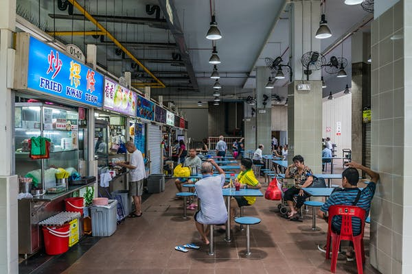 couple of elderly sitting outside a stall in a hawker centre