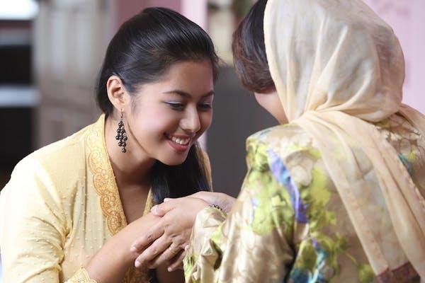 a young Malay lady in kebaya, seeking forgiveness from an older lady in baju kurung, wearing a head scarf