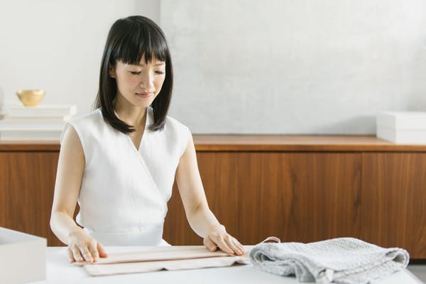 asian woman folding clothes neatly