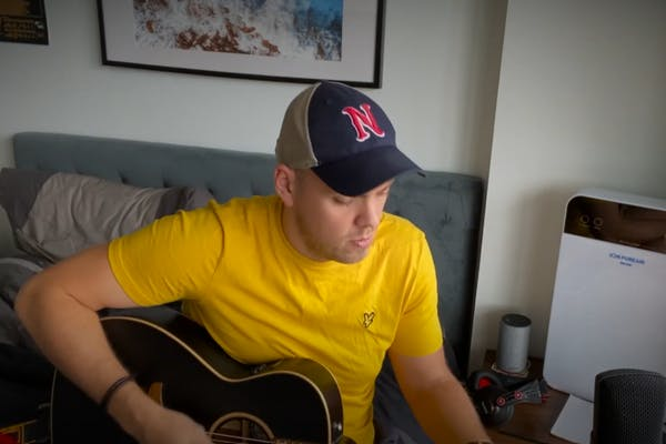 Jake in a yellow tee, playing and singing a cover of a song on bed, in his room