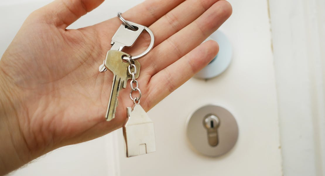a hand holding keys to a home
