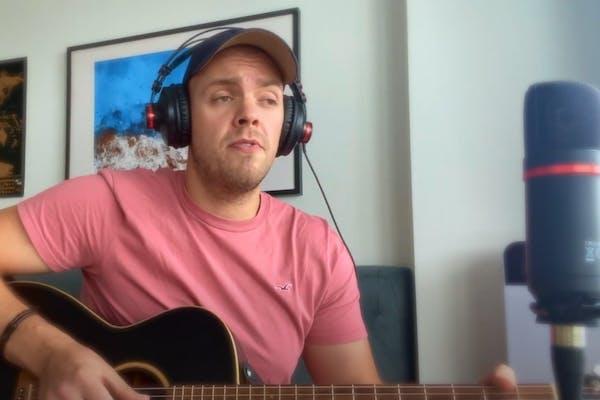 Jake wearing headphone over a cap, in pink tee, strumming his acoustic guitar.