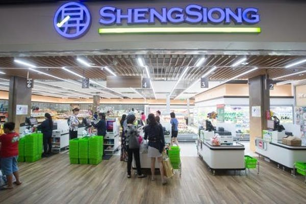 Sheng Siong supermarket check-out counters, with green baskets piled up beside the cashiers