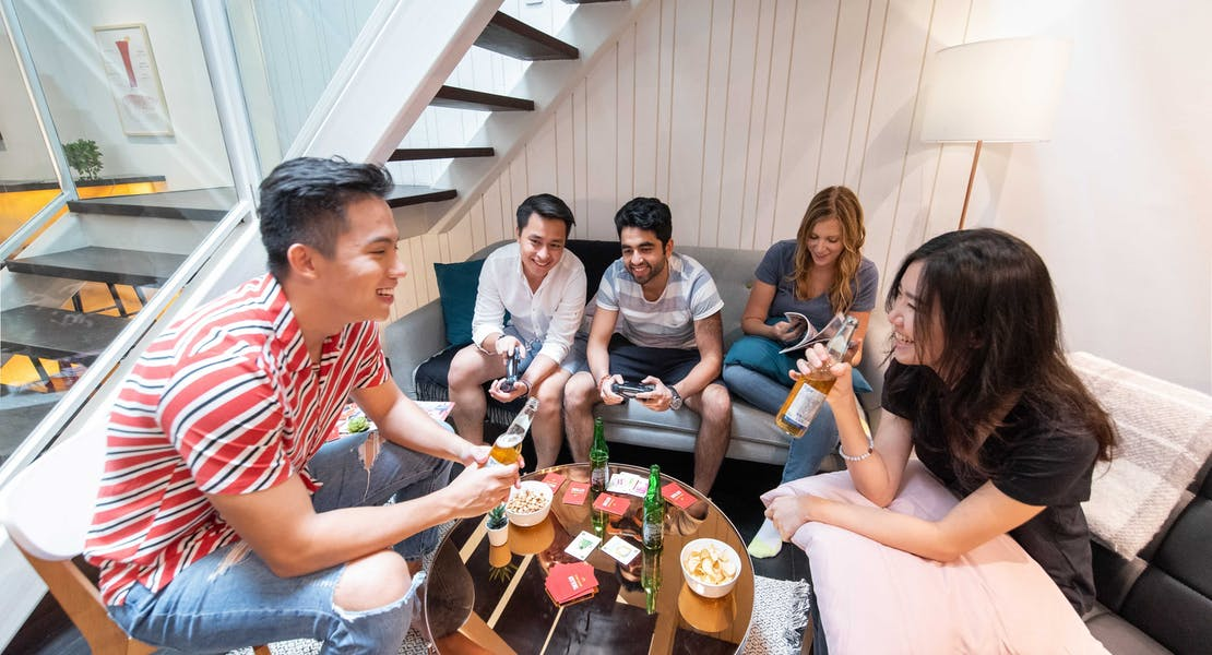 Group of friends in the living room enjoying beer and playing games