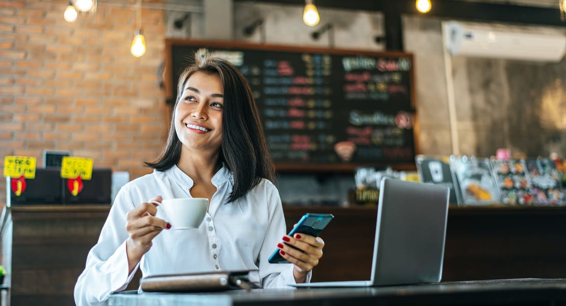 woman sitting at a cafe, enjoying her coffee while holding her phone and her laptop by the side