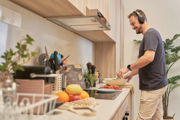 a man listening to music on his headphone, happily tossing a salad in the kitchen