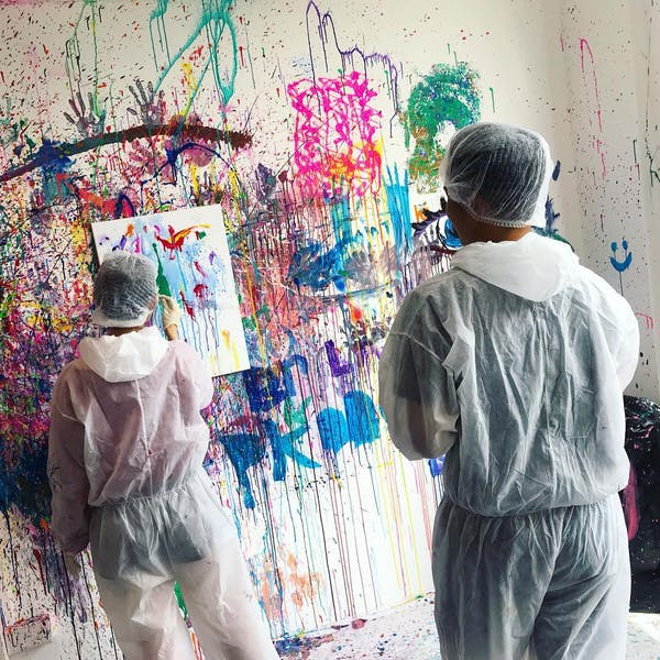 couple painting messily over a white canvas
